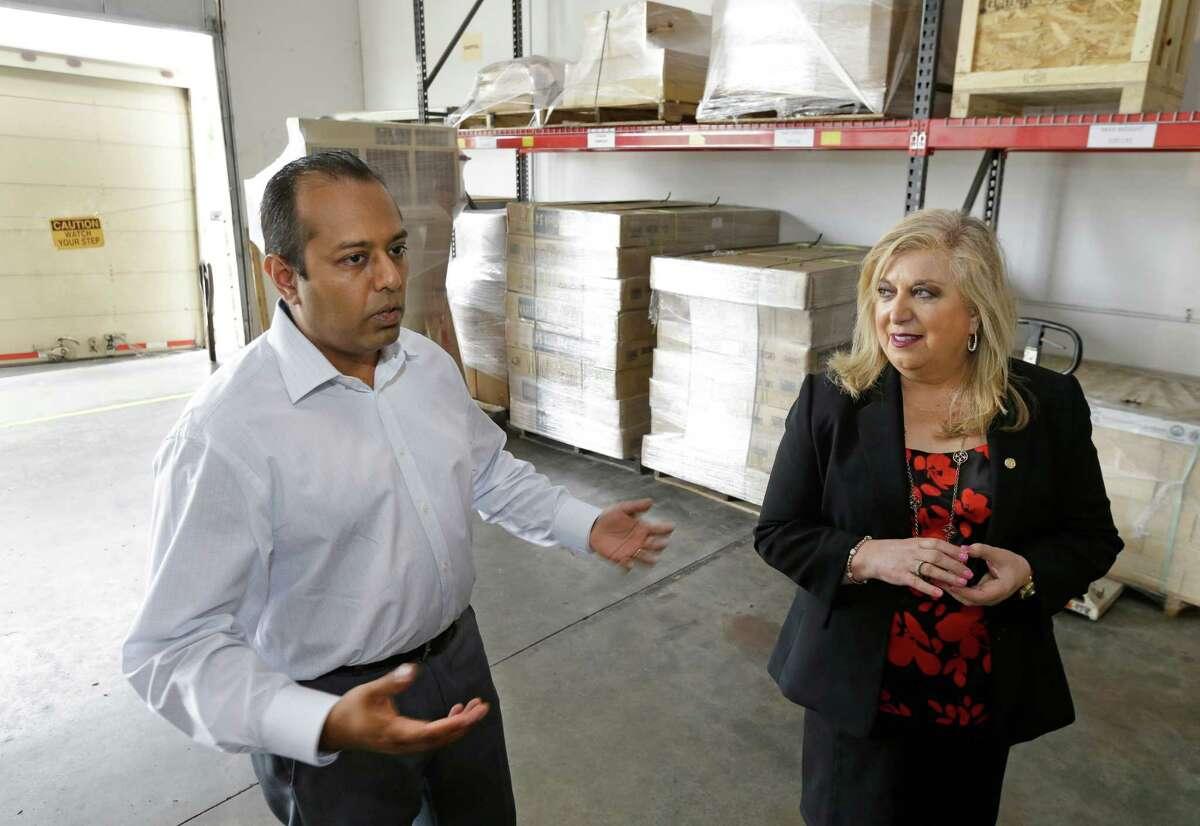 Sadik Dalal, left, CEO of Axistrade, and Yolanda Garcia Olivarez, right, U.S. Small Business Administration South Central Regional Administrator, talk at Axistrade, 16111 Park Entry Drive, Wednesday, May 11, 2016, in Houston. ( Melissa Phillip / Houston Chronicle )