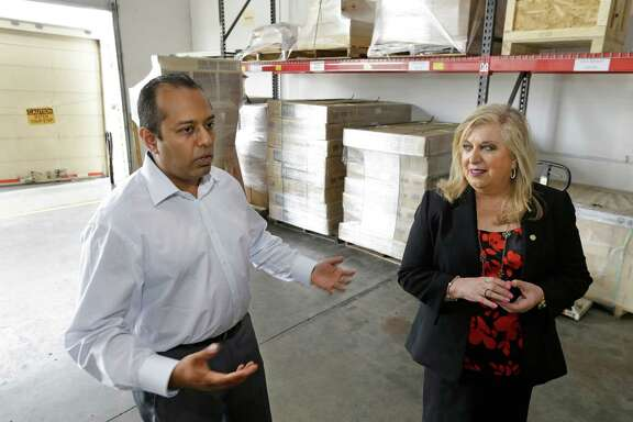 Sadik Dalal, left, CEO of Axistrade, and Yolanda Garcia Olivarez, right, U.S. Small Business Administration South Central Regional Administrator, talk at Axistrade, 16111 Park Entry Drive, Wednesday, May 11, 2016, in Houston.  ( Melissa Phillip / Houston Chronicle )