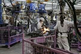 Employees weld parts of Honda Civic vehicles as they work on the production line of the Honda Motor Co. assembly plant in Prachinburi, Thailand, on Thursday, May 12, 2016. The new facility will have a maximum production capacity of 120,000 vehicles per year. Photographer: Dario Pignatelli/Bloomberg