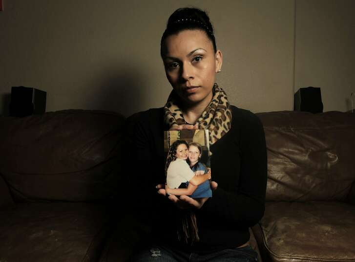 Erica Aguilar who was like a second mother to Raquel holds a middle school photograph of Raquel and Bobbie, while at the home of Raquel's  father in San Leandro, Calif. home on Thursday Jan. 3,  2013.  Raquel Gerstel and her friend Bobbie Sartain were shot and killed in a double homicide in Oakland, Ca. on Nov. 25, 2012.