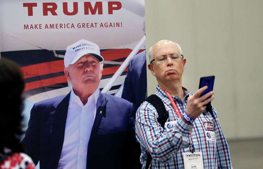 Glen Hettinger makes a photo of himself with a photo of Donald Trump in the exhibition hall during the Texas Republican Convention Thursday, May 12, 2016, in Dallas. (AP Photo/LM Otero) Photo: LM Otero, STF / Associated Press / Copyright 2016 The Associated Press. All rights reserved. This material may not be published, broadcast, rewritten or redistribu