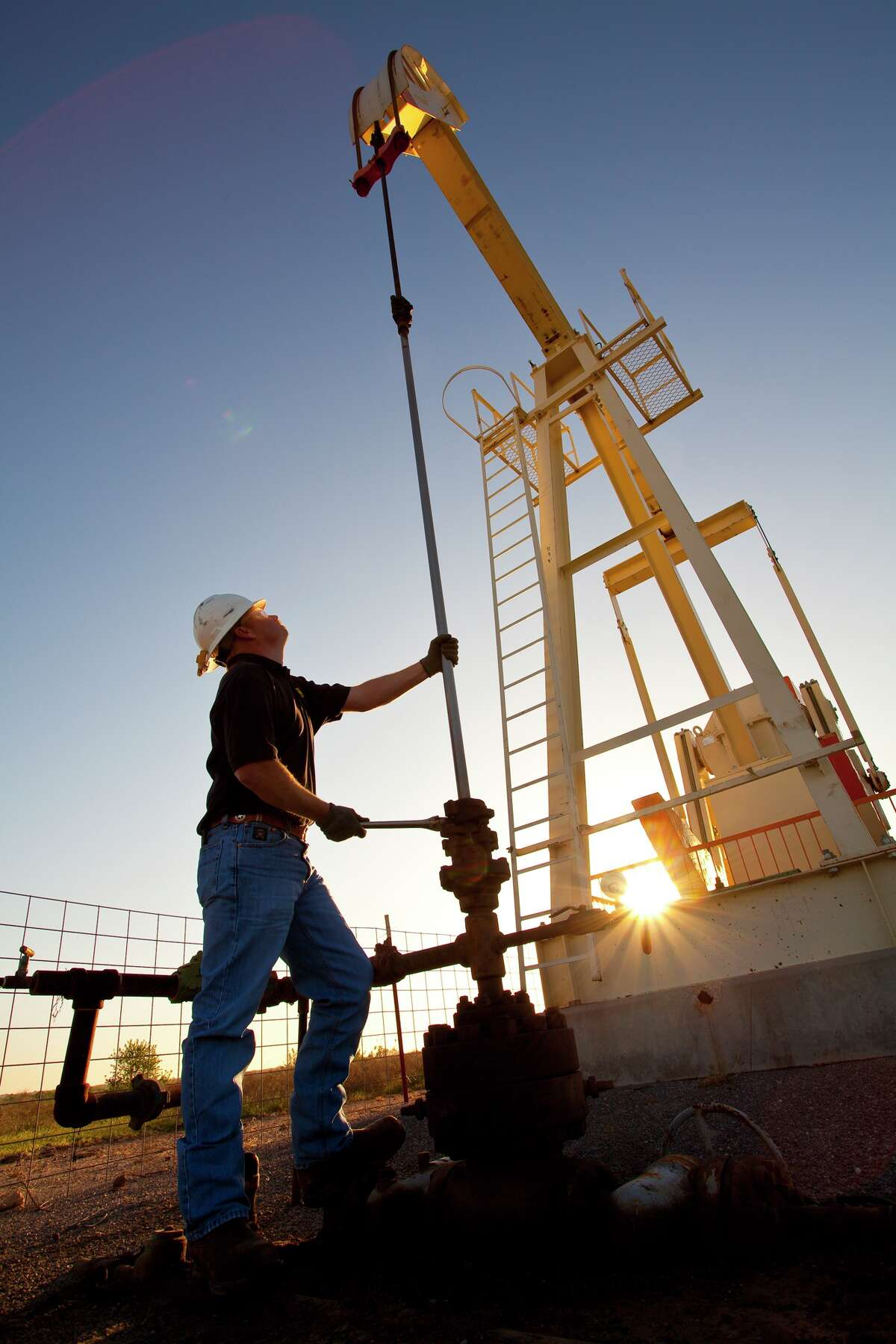 A pump jack looms over a worker at a Linn Energy site in the Permian Basin of West Texas. Much of the increase in drilling activity has been in the Permian.