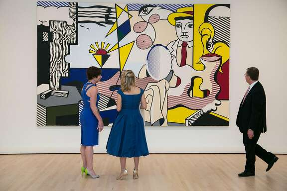 """From left: Nancy Finn, Danna Slusky and her husband Alex Slusky check out """"Figures with Sunset,"""" a 1978 painting by Roy Lichtenstein, during The Modern Ball 2016 at SFMOMA on Thursday, May 12, 2016 in San Francisco, Calif."""