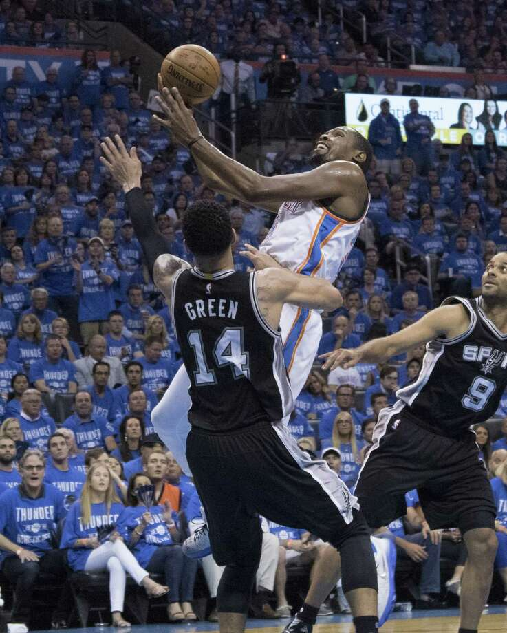 OKLAHOMA CITY, OK - MAY 12: Kevin Durant #35 of the Oklahoma City Thunder goes over Danny Green #14 of the San Antonio Spurs for two points during the first half ofGame Six of the Western Conference Semifinals during the 2016 NBA Playoffs at the Chesapeake Energy Arena on May 12, 2016 in Oklahoma City, Oklahoma.   NOTE TO USER: User expressly acknowledges and agrees that, by downloading and or using this photograph, User is consenting to the terms and conditions of the Getty Images License Agreement. (Photo by J Pat Carter/Getty Images) ORG XMIT: 633653407 Photo: J Pat Carter / 2016 Getty Images