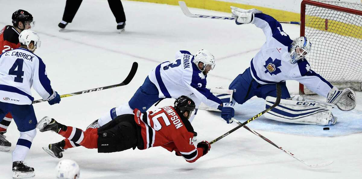 Devils' Paul Thompson, center, stretches out to score on Marlies goaltender Antoine Bibeau, right, during Game 5 of the American Hockey League quarterfinal playoff series on Thursday, May 12, 2016, at Times Union Center in Albany, N.Y. (Cindy Schultz / Times Union)