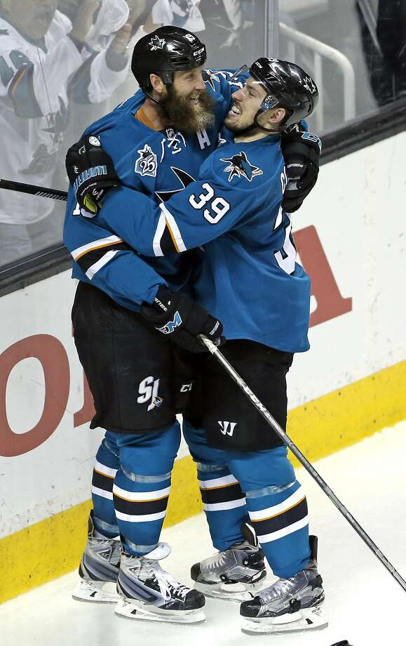 Logan Couture (39) helps Joe Thornton celebrate his goal in Thursday's Game 7 win. Photo: Scott Strazzante, The Chronicle