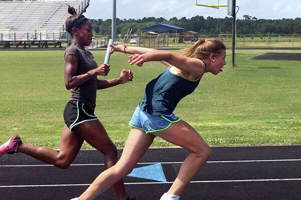 Raylie Huff, right, snatches the baton from teammate Wreagan Taylor as the Hardin-Jefferson duo practice for this weekend's relays at the state meet in Austin. (David Thompson/The Enterprise)