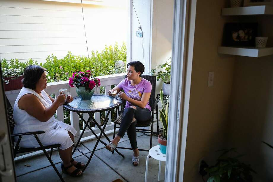 Middle school teachers Raquel Arcinas Clark and Reyna Jones drink coffee together on Jones' porch. Photo: Gabrielle Lurie, Special To The Chronicle