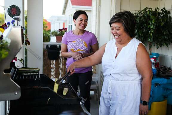 (l-r) Middle School teachers Reyna Jones and Raquel Clark laugh as they grill on Raquel's porch in Santa Clara, California, on Wednesday, May 11, 2016. They both live in the same subsided housing complex, which was provided by the Santa Clara School District.