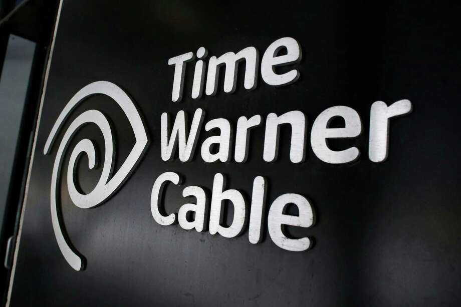 FILE - In this May 26, 2015, file photo, the Time Warner Cable corporate logo is displayed at a company store, in New York. On Monday, April 25, 2016, the Justice Department approved Charter's bid to buy Time Warner Cable and create another cable giant. Monday's OK comes with conditions meant to preserve competition from online services. Additional approvals are required, but expected, before the deal closes. (AP Photo/Mark Lennihan, File) Photo: Mark Lennihan / Associated Press / Copyright 2016 The Associated Press. All rights reserved. This material may not be published, broadcast, rewritten or redistribu