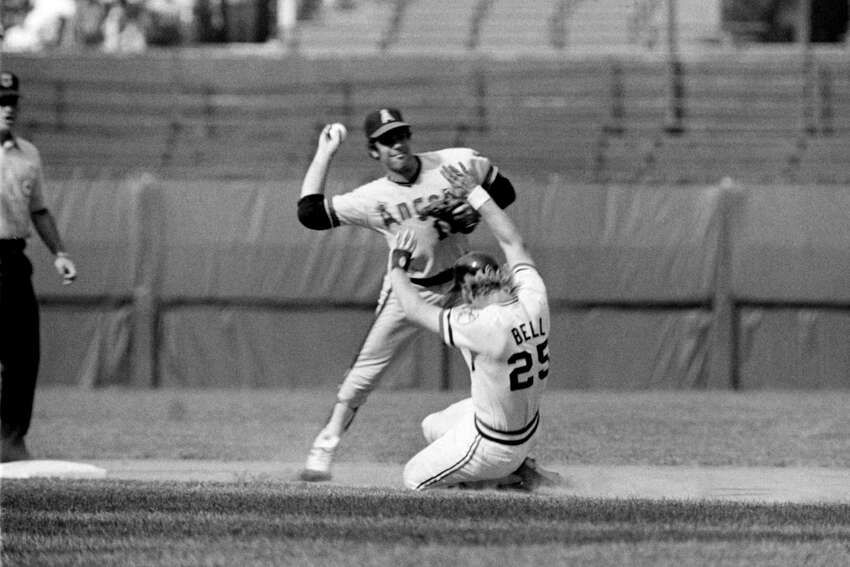 Shortstop Bobby Valentine #13 (right), of the California Angels, throws the ball to first base as Buddy Bell #25 (center), of the Cleveland Indians, is out trying to break up a double play at second base during a game on July 8, 1973 at Municipal Stadium in Cleveland, Ohio.