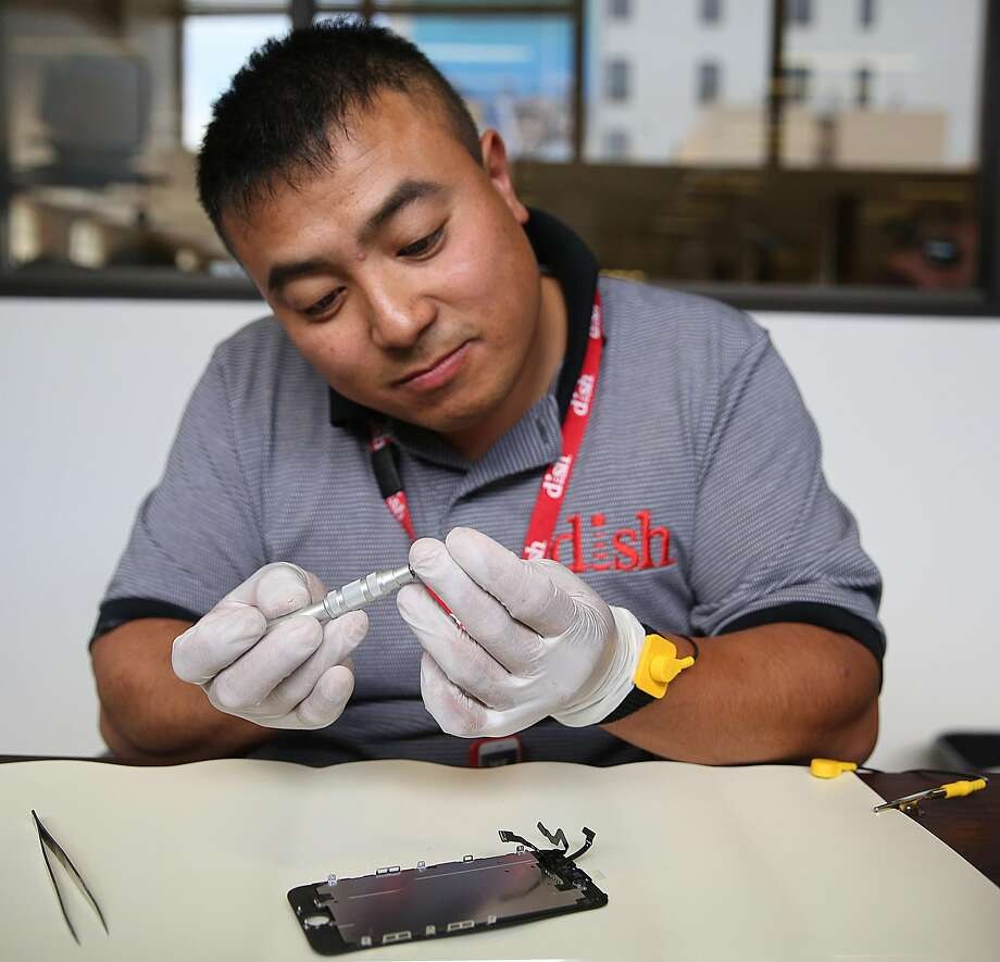 Dish employee Johnson Chuong takes apart an iPhone to fix a cracked screen on site in the Chronicle building. Photo: Liz Hafalia, The Chronicle