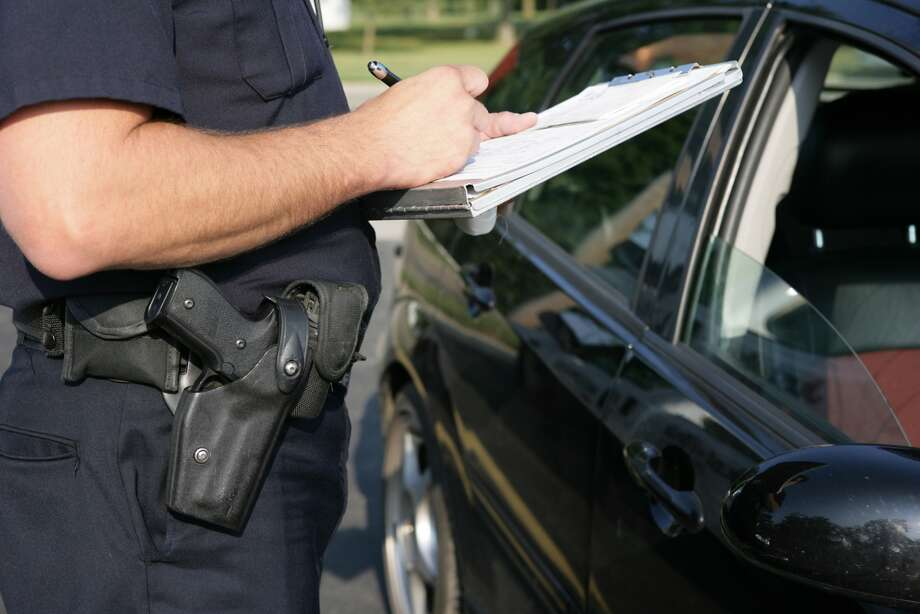 A police officer tickets a driver.
