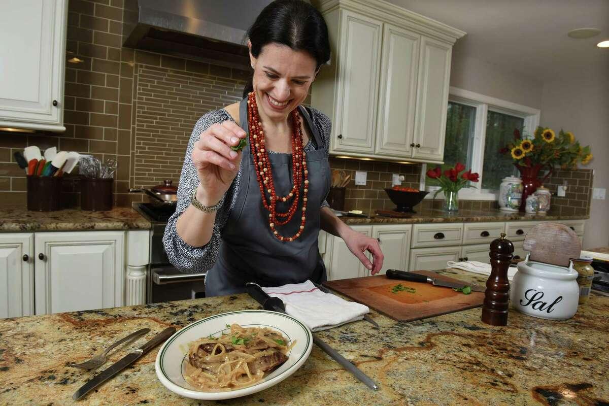 Leticia Moreinos Schwartz cooks two of her Brazilian recipes at home in Weston. Moreinos Schwartz uses parsley to garnish her steak with onion-mustard sauce.
