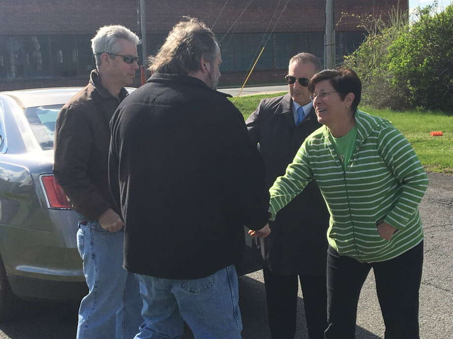 Green Island Mayor Ellen McNulty-Ryan, right, greets UAW Local 1508 president Tim Vogt Monday across the street from the Honeywell Aerospace factory.