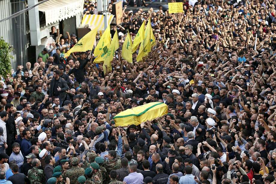 Supporters carry the coffin of slain military commander Mustafa Badreddine, draped in a Hezbollah flag, during his funeral procession in a Beirut. Photo: Hassan Ammar, Associated Press