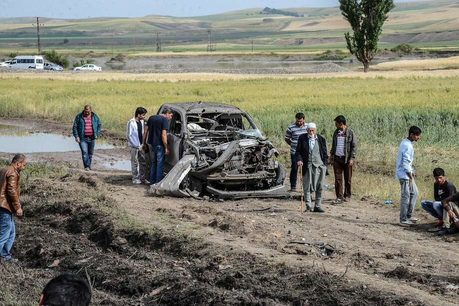 People look at a burnt car after a powerful blast outside the majority Kurdish city of Diyarbakir. Photo: ILYAS AKENGIN, AFP/Getty Images
