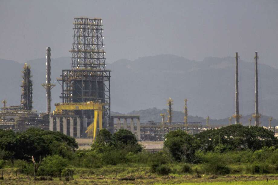 Petrobras's Comperj oil refinery stands behind a farm in Itaborai, Brazil, on Tuesday, April 12, 2016. Prosecutors in the U.S. and Brazil are effectively dividing the investigation of corruption at Brazil's giant state-run oil company to suit their respective strengths as they pursue suspected graft at Petrobras. Photo: Dado Galdieri /Bloomberg / © 2016 Bloomberg Finance LP