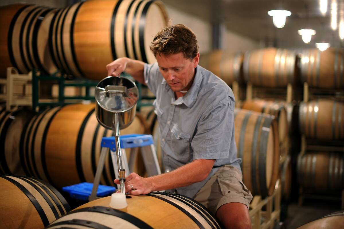 Winemaker Wells Guthrie topping off French oak barrels with pinot noir for a 2010 vintage at Copain Winery in Healdsburg.