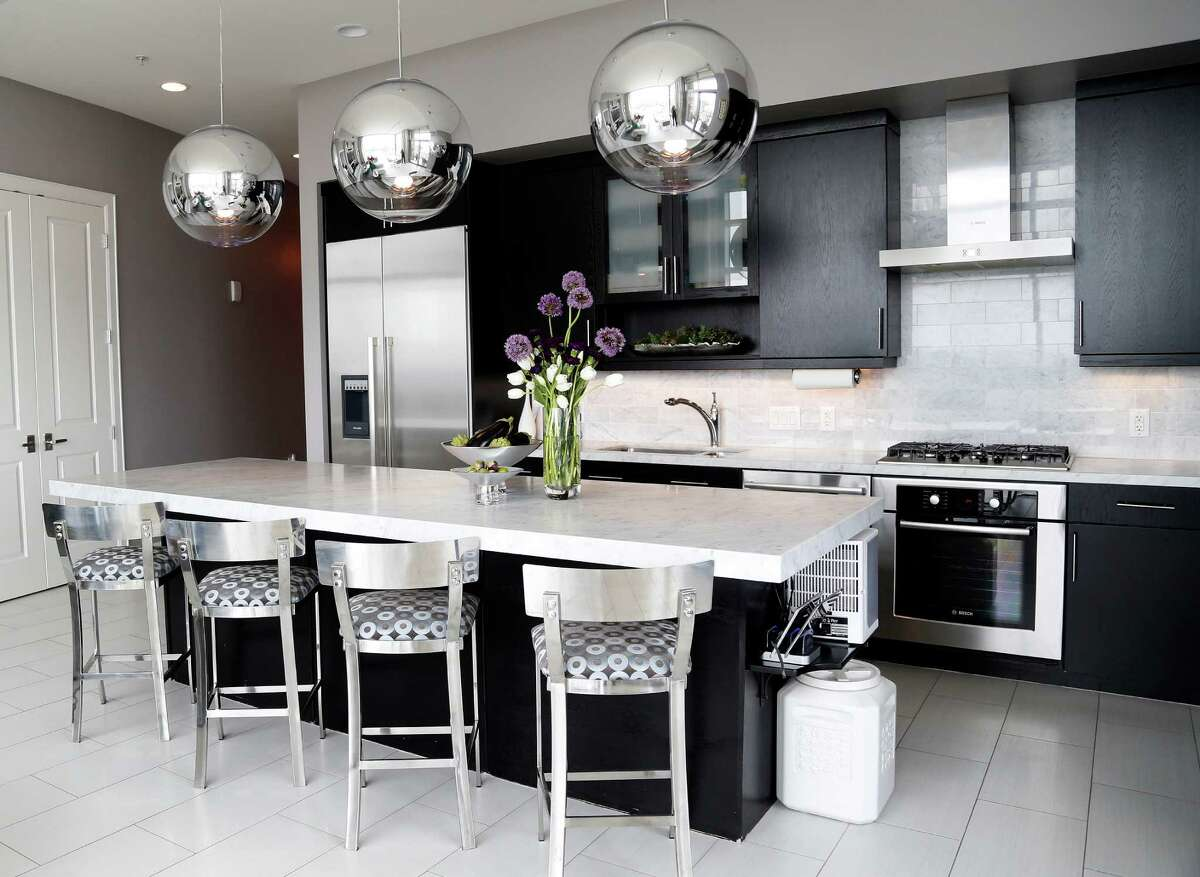 SILVER ACCENTS: A modern aesthetic gives this kitchen a unique look. See the rest of the home at houstonchronicle.com: Dentists downsized from West U traditional to penthouse posh