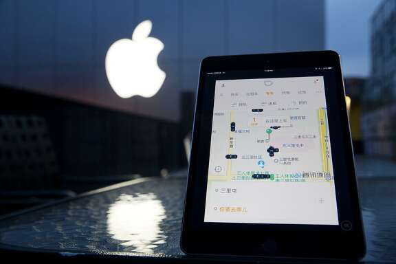 A mobile device displaying the Didi Chuxing app is posed near the Apple store logo in Beijing, China, Friday, May 13, 2016. Apple Inc. has invested $1 billion in Chinese ride-hailing service Didi Chuxing, the main competitor in China for Uber Technologies Ltd. (AP Photo/Ng Han Guan)
