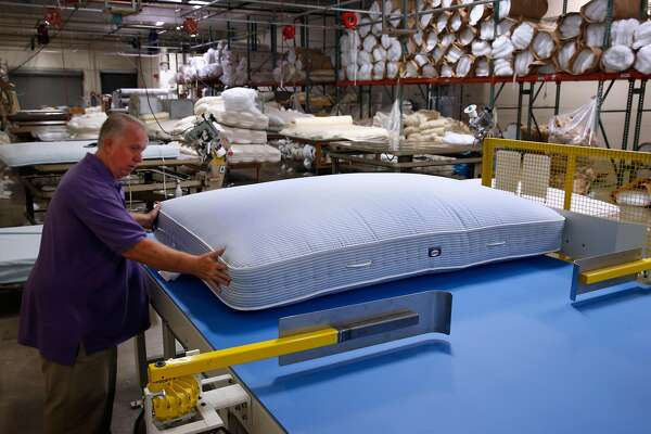 Plant manager Paul Deming aligns a mattress onto a tufting machine at the McRoskey Mattress Company in San Francisco, Calif. on Friday, May 13, 2016.