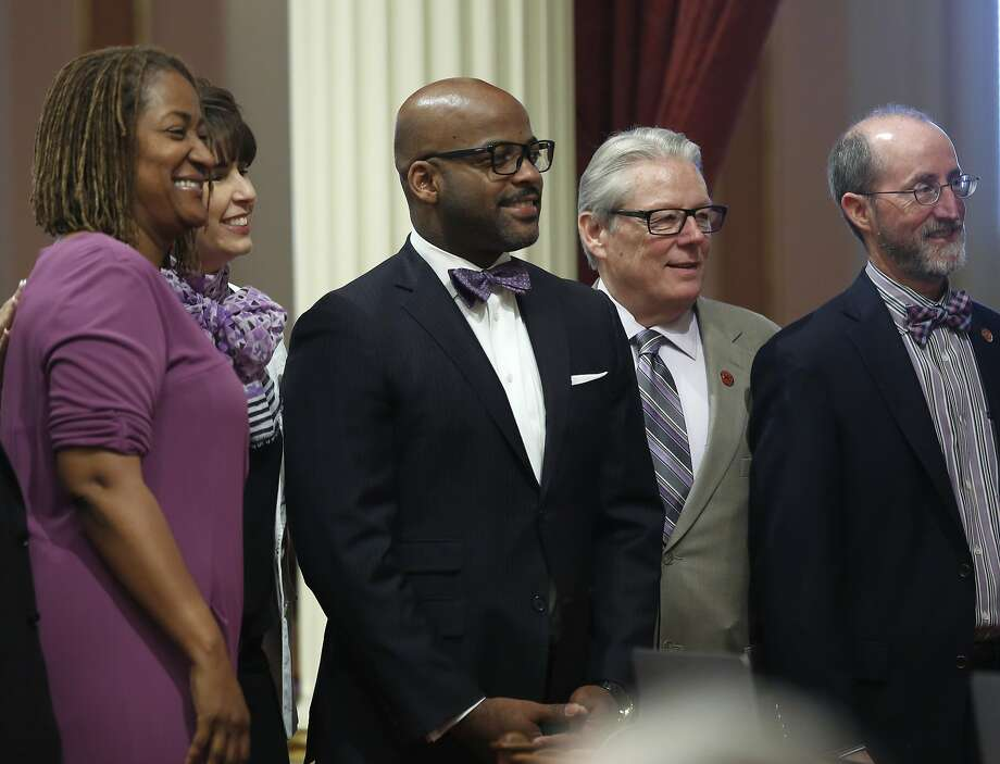 Wearing purple in one manner or another, California Democratic state senators, from left, Holly Mitchell, of Los Angeles, Connie Leyva, of Chino, Isadore Hall III of Compton, William Monning of Carmel, and Steven Glazer of Orinda, pose for a photo during the Senate session at the Capitol, Thursday, May 12, 2016, in Sacramento, Calif. Hall and the others wore purple to remember the late musician Prince, who was found dead in his Minnesota home last month. (AP Photo/Rich Pedroncelli) Photo: Rich Pedroncelli, Associated Press