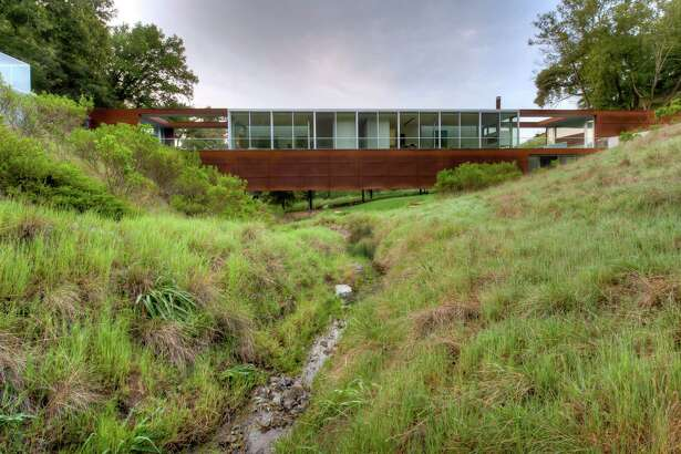 Studio Green restored the seasonal creek that trickles beneath his Marin County home surrounded by coastal redwoods and oak trees.Trails around the property lead to a pool and bocce court.