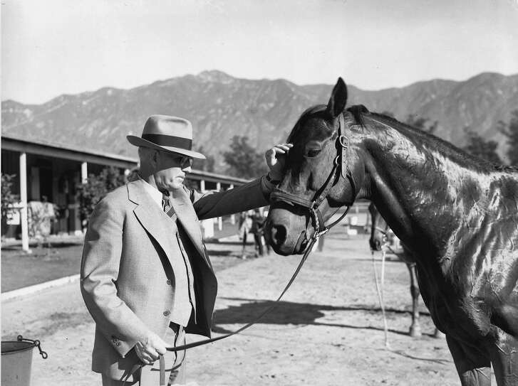 This is an undated photo showing Seabiscuit and trainer Tom Smith, at an unknown location. The leather saddle worn by Seabiscuit and Australian champion Phar Lap and the riding silks and crop that belonged to jockey George Woolf will be sold at auction this Sunday July 20, 2003 in Beverly Hills, Calif. (AP Photo/File)