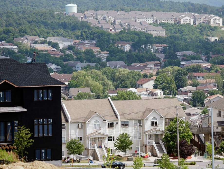 FILE - In this July 1, 2014, file photo, a new housing unit, left, is under construction in Kiryas Joel, N.Y. (AP Photo/Mike Groll, File) Photo: Mike Groll / AP