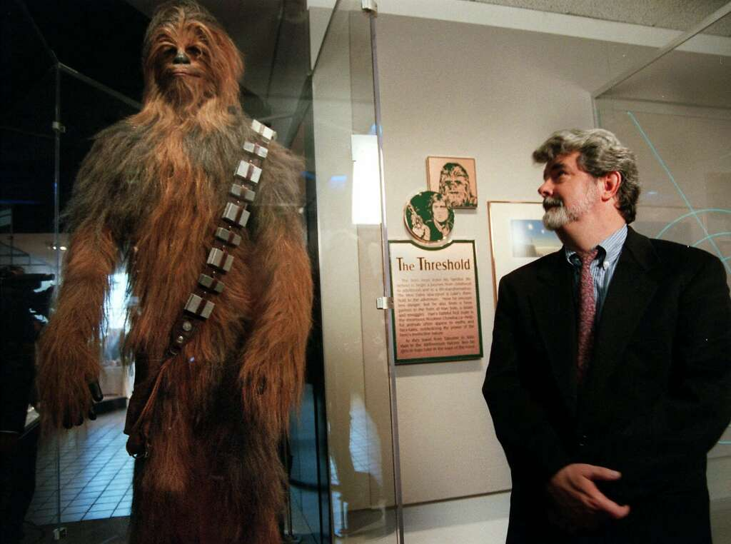"Moviemaker George Lucas looks over Chewbacca at the ""Star Wars"" exhibit at the Smithsonian Institution's Air and Space Museum in 1997. Photo: KEN CEDENO, AP"