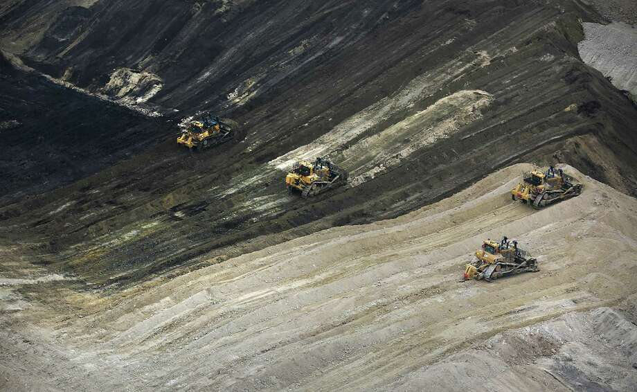 Large bulldozers move dirt to expose coal at the Dos Republicas Coal Mine just outside the Texas-Mexico border city of Eagle Pass. The mine has in its first six months shipped 1 million tons of coal across the border to Mexico, . Photo: Bob Owen /San Antonio Express-News / San Antonio Express-News