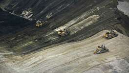 Large bulldozers move dirt to expose coal at the Dos Republicas Coal Mine just outside the Texas-Mexico border city of Eagle Pass. The mine has in its first six months shipped 1 million tons of coal across the border to Mexico, .