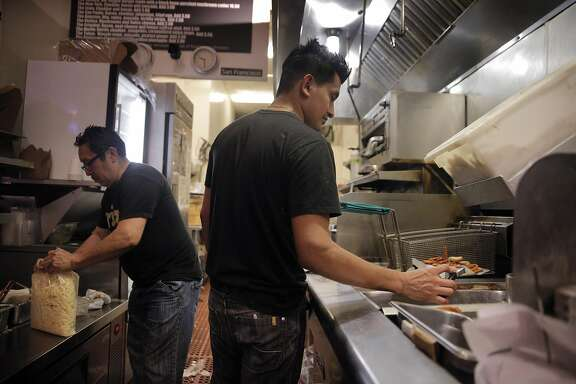 Oscar Ku refills work stations with food items as Gilson Hernandez prepares an order on the line at Frjtz restaurant in San Francisco, Calif., on Wednesday, May 4, 2016.