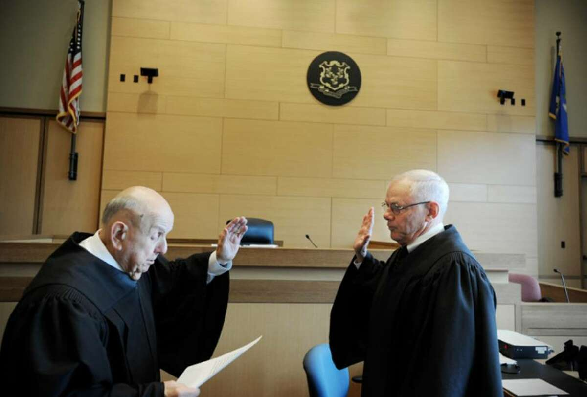 Criminal judges Martin L. Nigro and Richard F. Comerford, Jr. swear each other in to 8 year terms at Stamford State Superior Court in Stamford, Conn. on Thursday April 15, 2010.