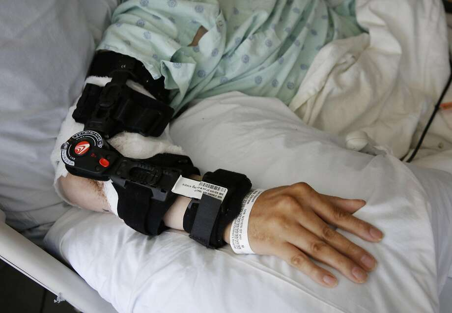 Reginald Cook rests his arm, which features an elbow transplanted from his left arm, on pillows at UCSF Medical Center. Photo: Leah Millis, The Chronicle