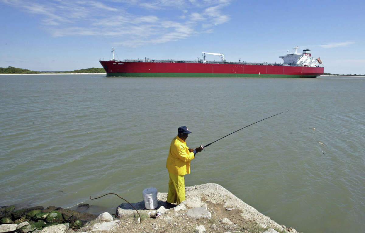The SKS Trent oil tanker passes through the Houston Ship Channel near Morgan's Point, Texas as Ed Phillip fishes on October 14, 2004. Crude oil rose to a record $54.76 a barrel in New York after an Energy Department report showed that U.S. supplies of heating oil plunged last week. Photographer: Craig Hartley/Bloomberg News