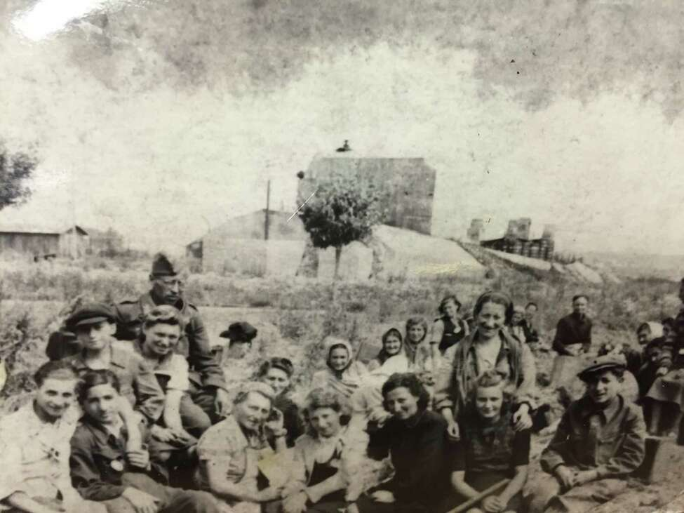 Henry Brenner pcitured here as a young boy (second row, far left, in cap) in 1939 with a group of Jews at a work camp outside his hometown of Demblin, Poland in late 1939. (Photo courtesy of Holocaust Survivors and Friends Education Center)