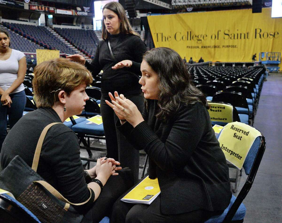 Blind and deaf, Quinn Burch, left, of Rotterdam, who will graduate with her class from the College of St. Rose and interpreters Shaily Cohen and Sandy Boettcher, right, prep for tomorrow's graduation ceremonies at the Times Union Center Friday May 13, 2016 in Albany, NY. (John Carl D'Annibale / Times Union)