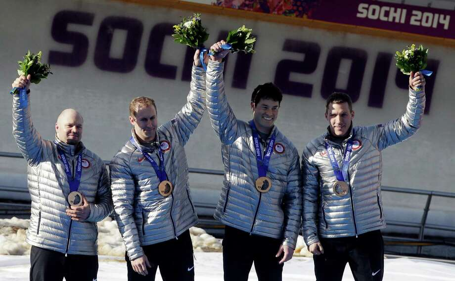 FILE - In this Feb. 23, 2014, file photo, members of the USA-1 team Steven Holcomb, left, Curtis Tomasevicz, Steven Langton and Christopher Fogt, celebrate after they won bronze in the men's four-man bobsled at the Winter Olympics in Krasnaya Polyana, Russia. Holcomb won two bronze medals at the Sochi Olympics that could be upgraded to silver if doping allegations against the Russians are proven. (AP Photo/Dita Alangkara, File) ORG XMIT: NY151 Photo: Dita Alangkara / AP