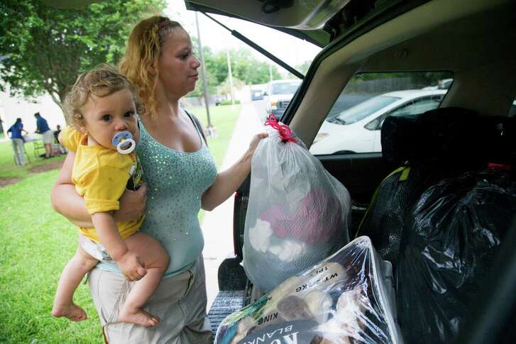 Told that she has until Sunday to move out of Baymont Inn & Suites on Sam Houston Parkway, Johanna Sanchez moves personal belongings while holding her son, Rafael. Sanchez says she needs the extra days because she has children with special needs.