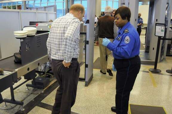 A TSA agent guides passengers through the TSA PreCheck line at Hobby Airport in 2013. Using this line lets the passenger go through an expedited screening line if they first submit to a government background check.