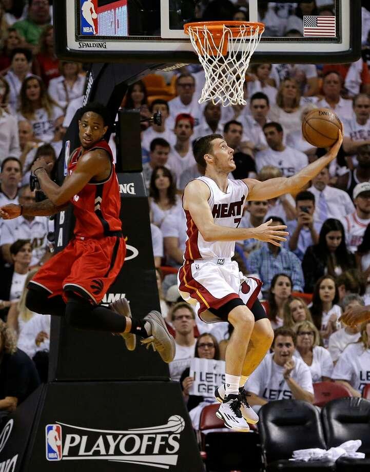 The Heat's Goran Dragic slips past the Raptors' DeMar DeRozan for a reverse layup on his way to a 30-point night. Photo: Alan Diaz, Associated Press