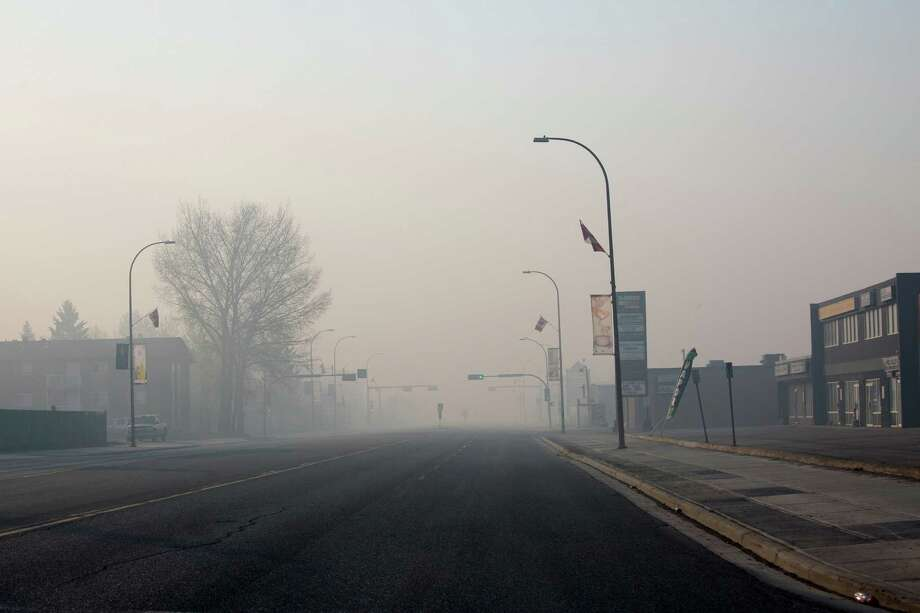 FILE — Smoke from a wildfire fills the street in deserted downtown Fort McMurray, Alberta, Canada, May 6, 2016. While the oil markets have remained relatively stable and production is slowly picking up, the economic blow from the wildfire is significant to a region and a country already battered by weak oil prices and uncertainty over the global growth. (Tyler Hicks/The New York Times) ORG XMIT: XNYT125 Photo: TYLER HICKS / NYTNS