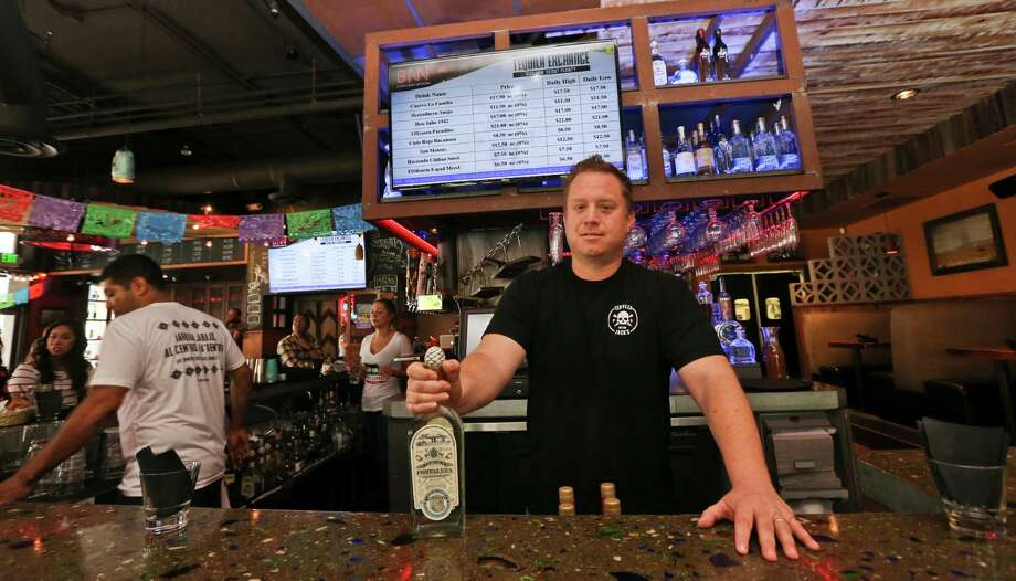 Frank Miller, shows off tequila at Naked Burro Bar, where prices change every five minutes based on sales.  Photo: Lenny Ignelzi, STF / Copyright 2016 The Associated Press. All rights reserved. This material may not be published, broadcast, rewritten or redistribu