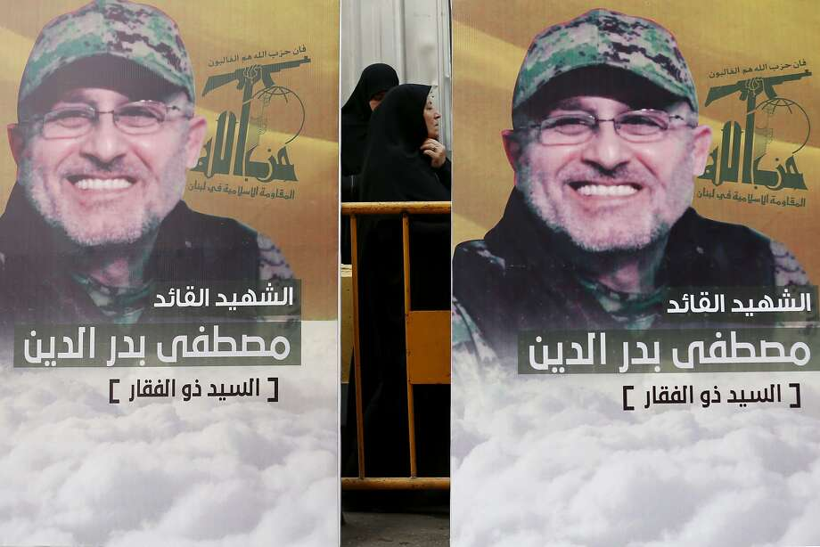 Pictures of slain commander Mustafa Badreddine hang during his funeral Friday in Beirut. Photo: Hassan Ammar, Associated Press
