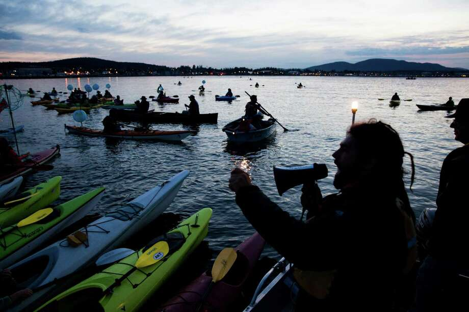 Eric Ross instructs 'kayak-tivists' to form a sign in with the Tesoro and Shell refineries behind them on Friday, May 13, 2016. Photo: GRANT HINDSLEY, SEATTLEPI.COM / SEATTLEPI.COM
