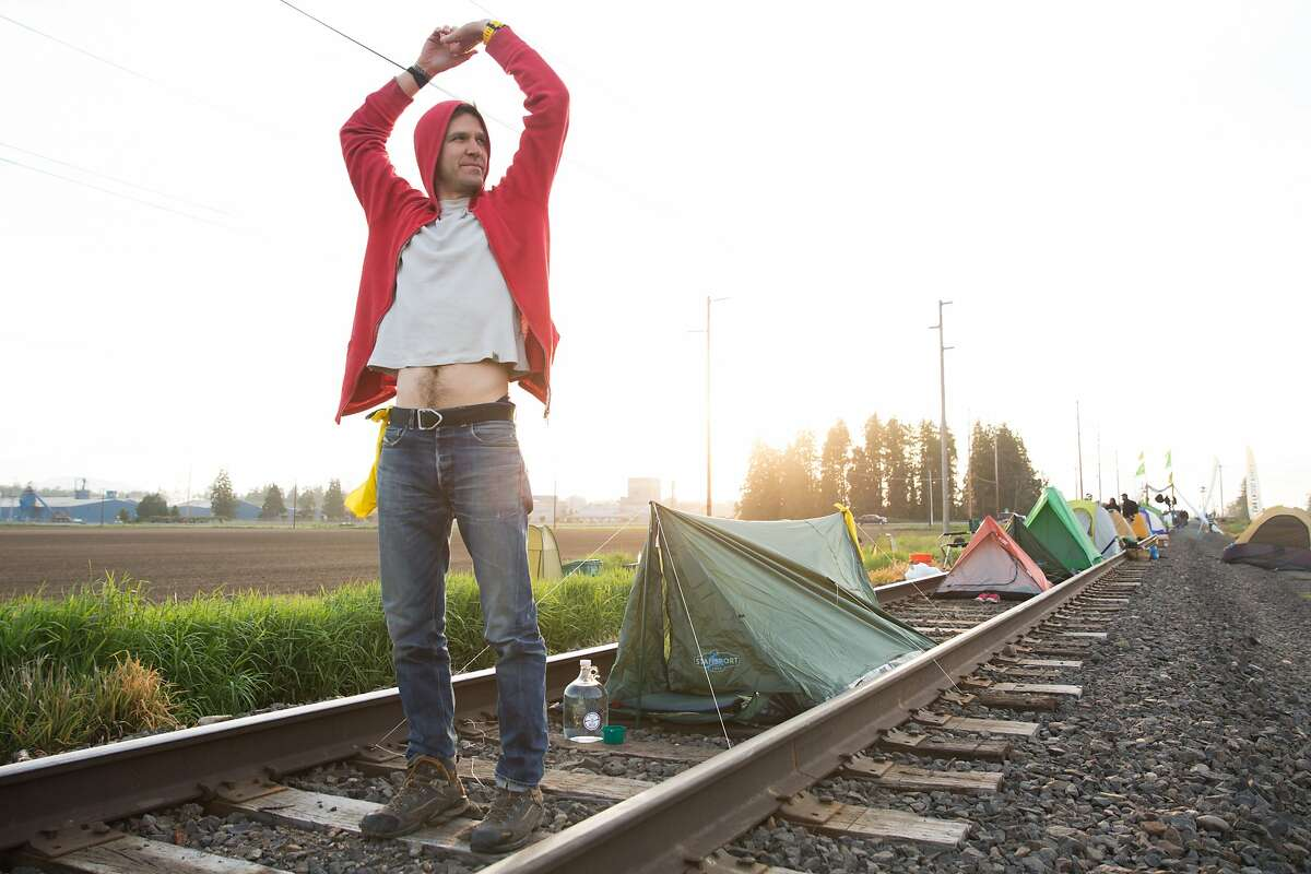 Matt Johnson of Seattle stretches after climbing out of his tent on the train tracks leading to the Tesoro refinery on March Point during Break Free PNW, early Saturday morning, May 14, 2016. (GRANT HINDSLEY, seattlepi.com)