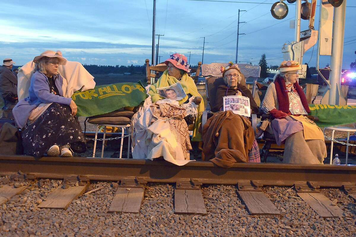 Members of the Seattle Raging Grannies sit in their rocking chairs chained together on the Burlington-Northern Railroad tracks at Farm to Market Road in Skagit County on Friday evening, May 13, 2016, in Burlington, Wash. From left are Deejay Sherman Peterson, Anne Thureson, Shirley Morrison and Rosy Betz-Zall. Hundreds of people in kayaks and on foot are gathering at the site of two oil refineries in Washington state to call for action on climate change and a fair transition away from fossil fuels. (Scott Terrell/Skagit Valley Herald via AP) MANDATORY CREDIT