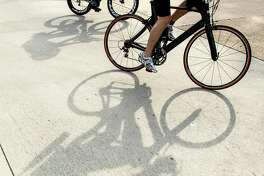 Cyclist cast their shadows on the race course during the Memorial Hermann Ironman North American Championship Texas triathon on Saturday, May 14, 2016, in The Woodlands.